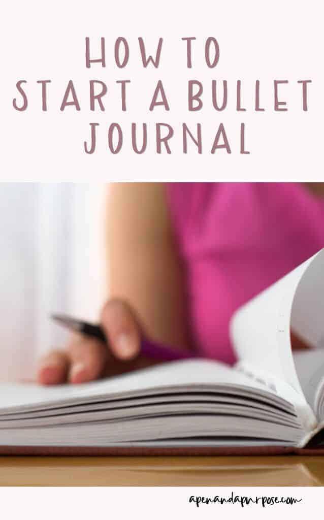 How to start a bullet journal. Woman starting journal holding a pen.