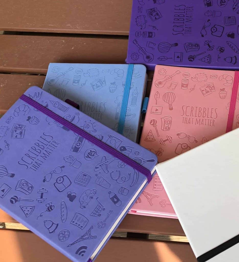 Scribbles That Matter Notebooks. A stack of Iconic Scribbles That Matter Notebooks in white, purple, pink, blue, and yellow